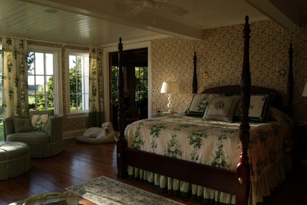 owner\'s bedroom with four poster bed and dog on floor