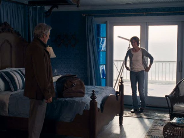 A man and a woman standing in front of a window, with Inn At Rodanthe