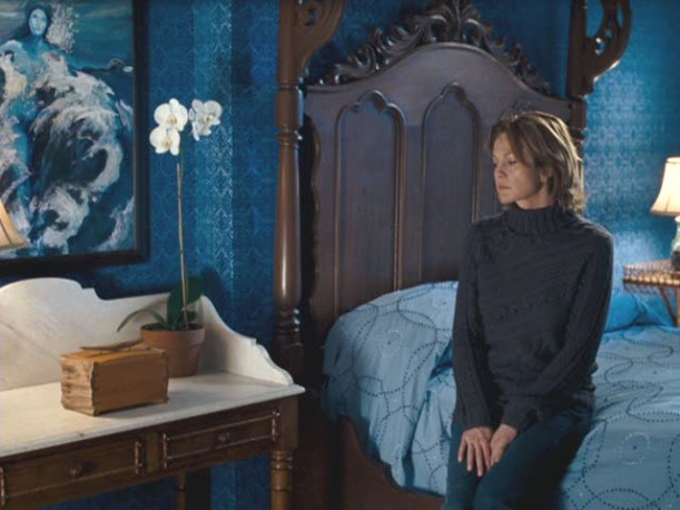Diane Lane sitting on a bed in the blue bedroom