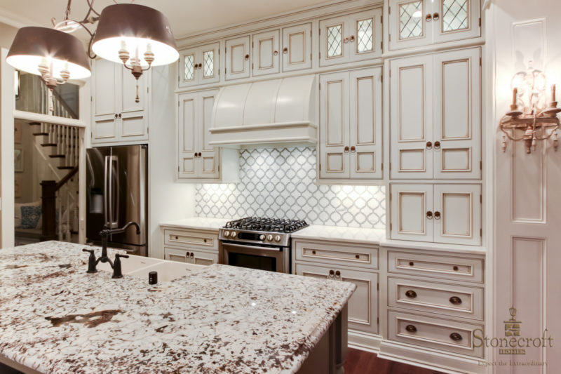 kitchen cabinets and large vent hood over range