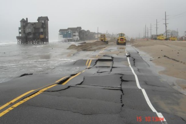 buckling road along the beach after storm
