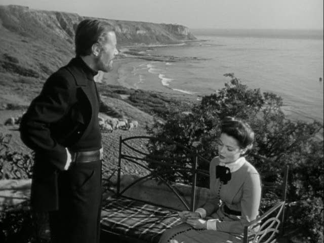 Rex Harrison and Gene Tierney in front of cottage overlooking the sea