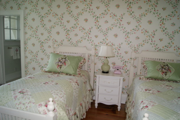 A bedroom with pink and green wallpaper