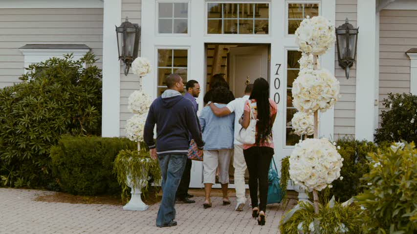 wedding guests walking through the front door of the house