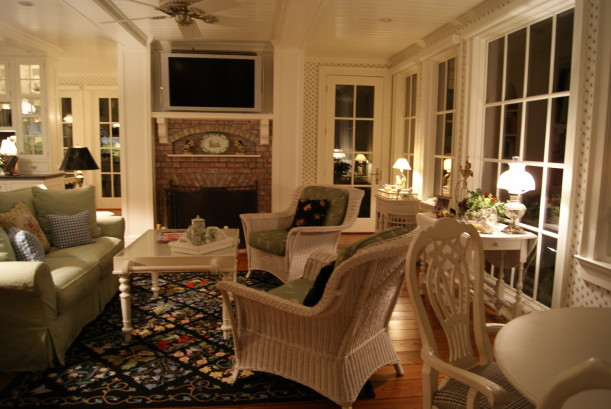 sunroom with wicker furniture and brick fireplace
