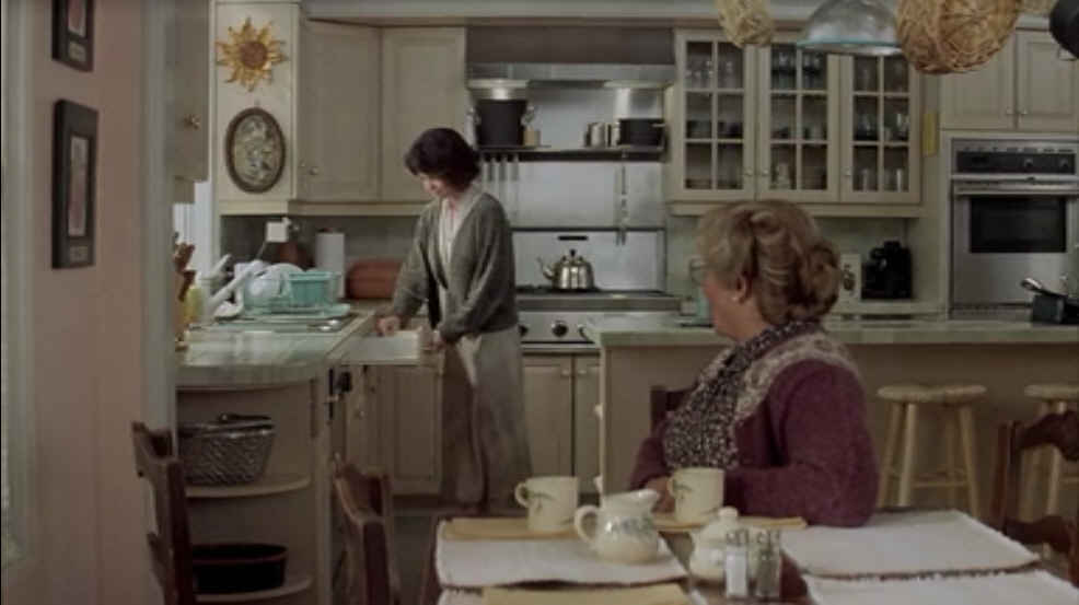 A person standing in a kitchen, with Mrs. Doubtfire