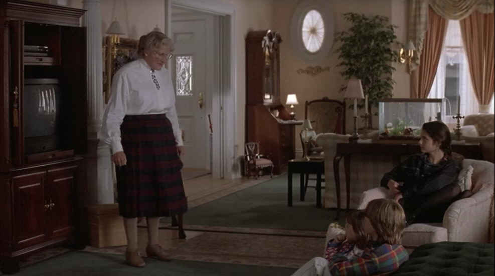 Mrs. Doubtfire standing in living room by TV