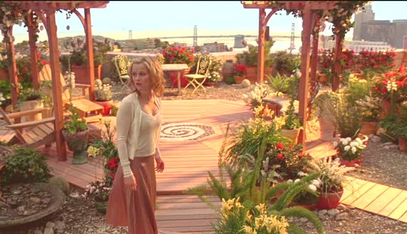 Reese Witherspoon standing on rooftop garden