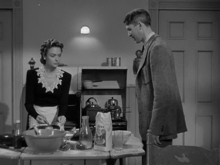 Mary and George Bailey standing in their kitchen while she bakes