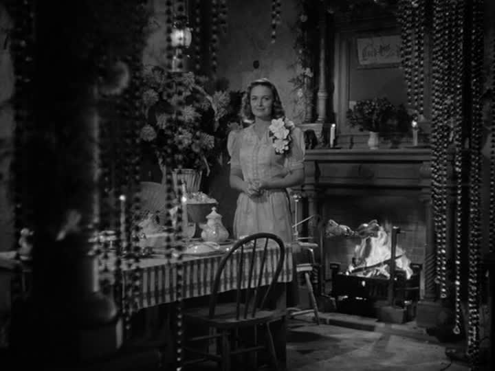 Mary Bailey stands in front of table beside fireplace