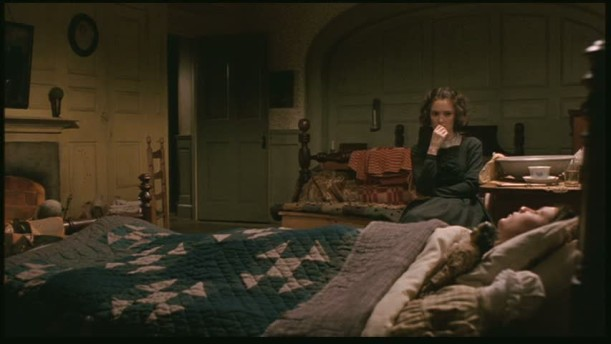 Winona Ryder sitting beside the bed