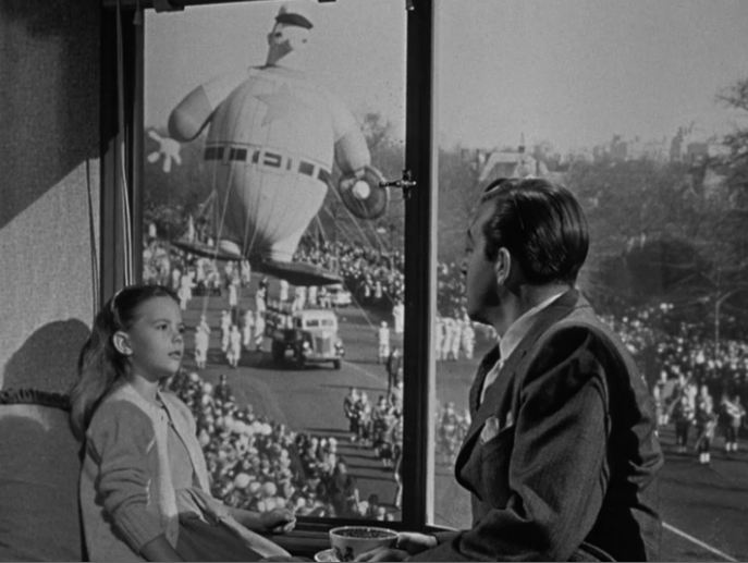 Susan watches the parade from John Payne\'s apartment