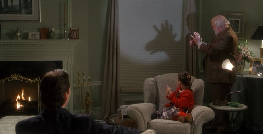 making shadow puppets on the wall of the apartment