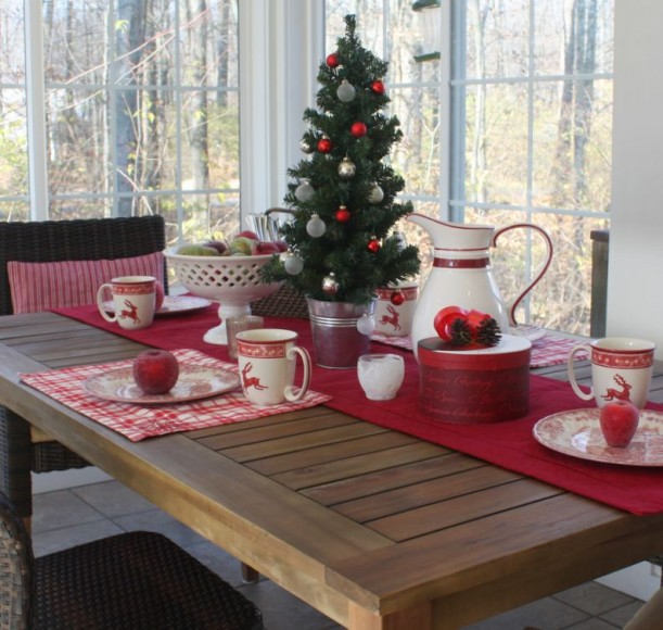 A dining room table in front of a window decorated for Christmas
