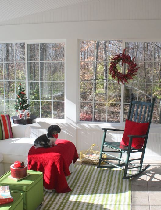 sunroom decorated for Christmas in red and green with dog on sofa