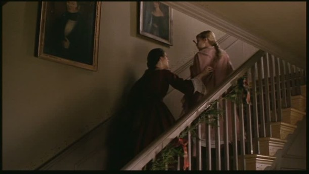 two sisters climbing the staircase decorated with garland for Christmas