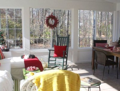 sunroom decorated for Christmas in red and green
