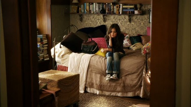 Aria sitting on her bed in her bedroom