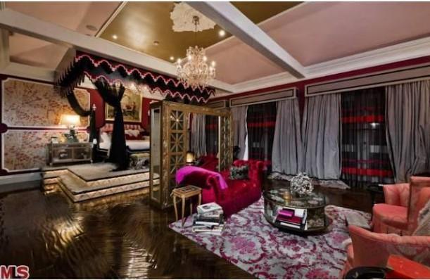 The Master Bedroom Has A Kind Of Black Canopy Bed On Platform