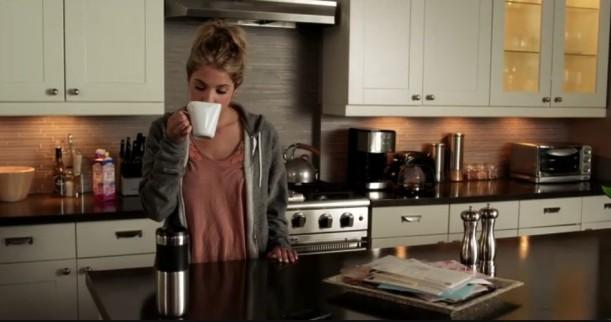 Hanna drinking coffee in her kitchen