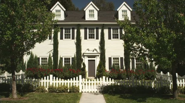 front exterior of Hanna\'s white house with black shutters and picket fence