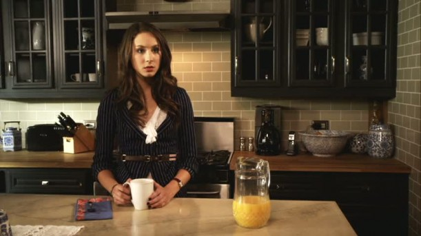 Spencer standing in her kitchen drinking coffee