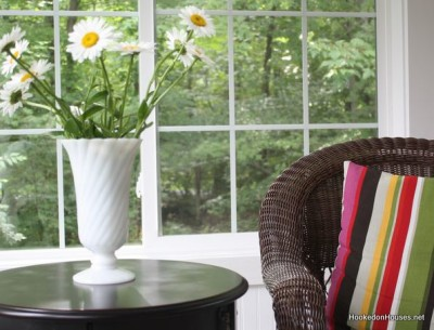 A vase of daisies in sunroom