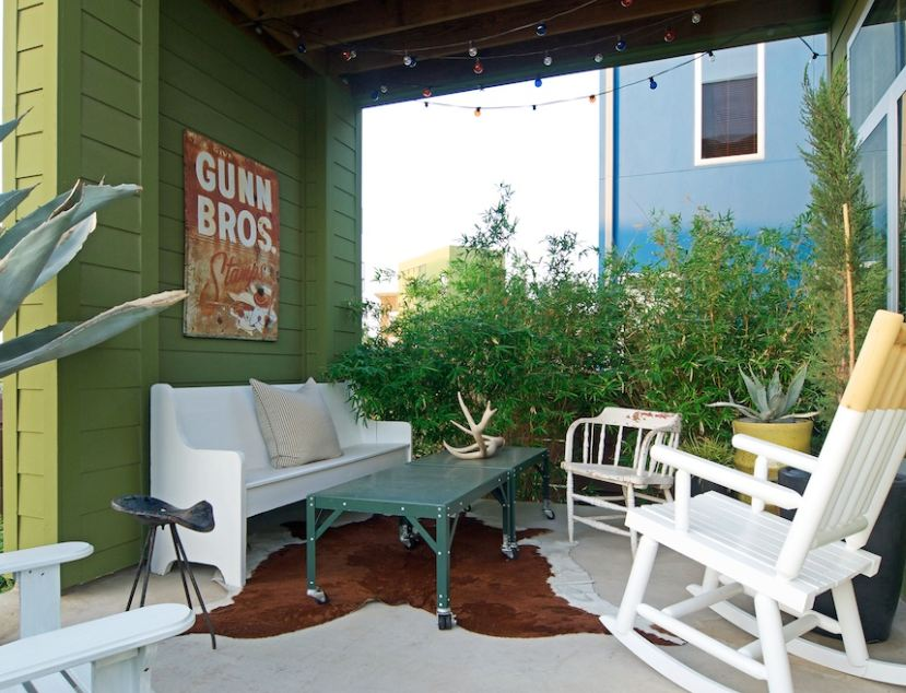 back patio with church pew painted white and rocking chairs