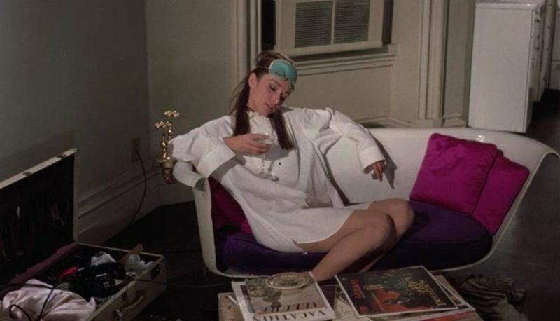 Audrey Hepburn sitting on white sofa