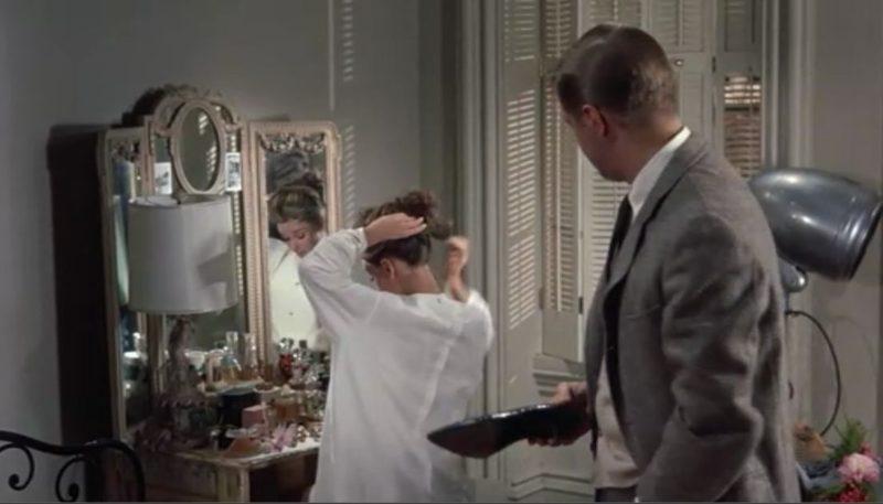 Audrey Hepburn standing at the mirrored vanity
