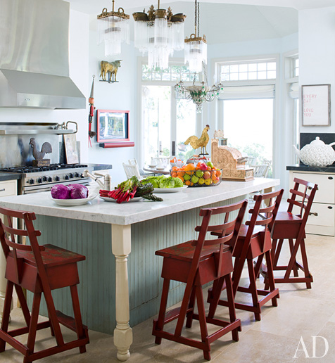 kitchen with pale blue island and red barstools