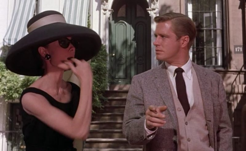 Holly Golightly whistling for a cab in front of apartment building