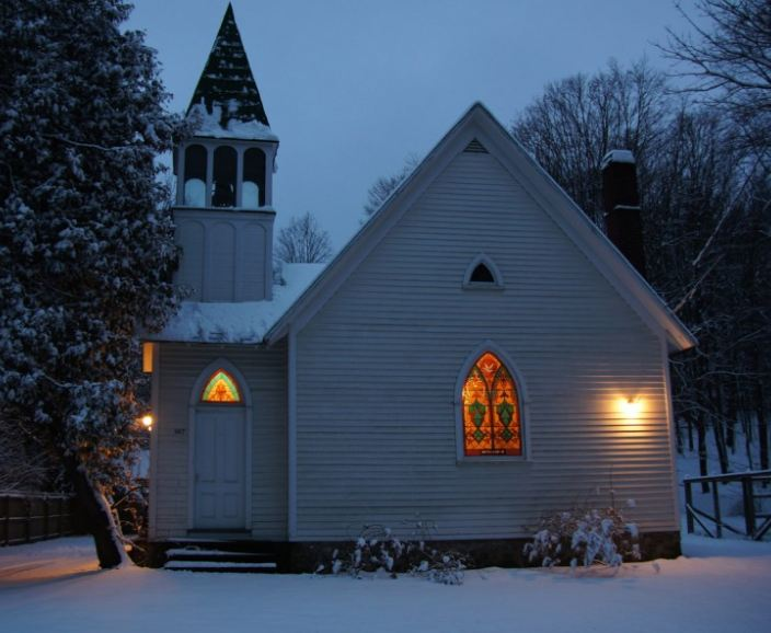 the converted church covered in snow at night with lights