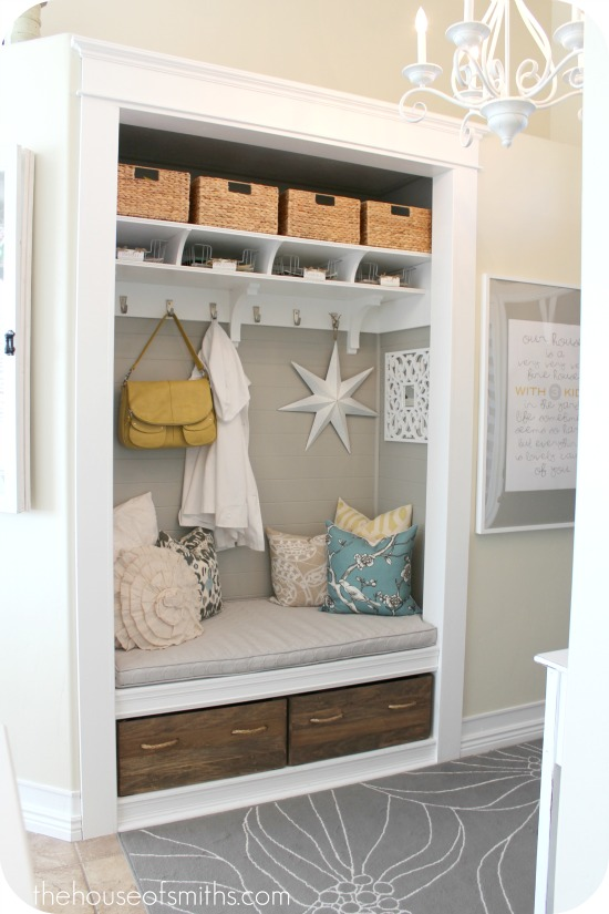 new mudroom nook in entry hall with padded bench, hooks and cubbies