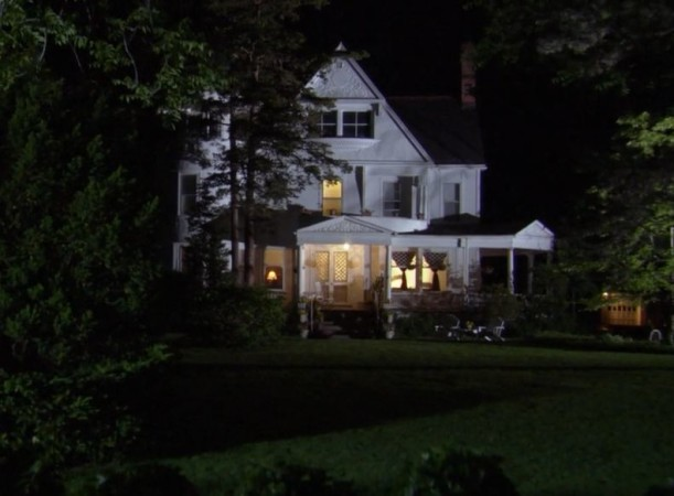 exterior of white farmhouse at night with lights on