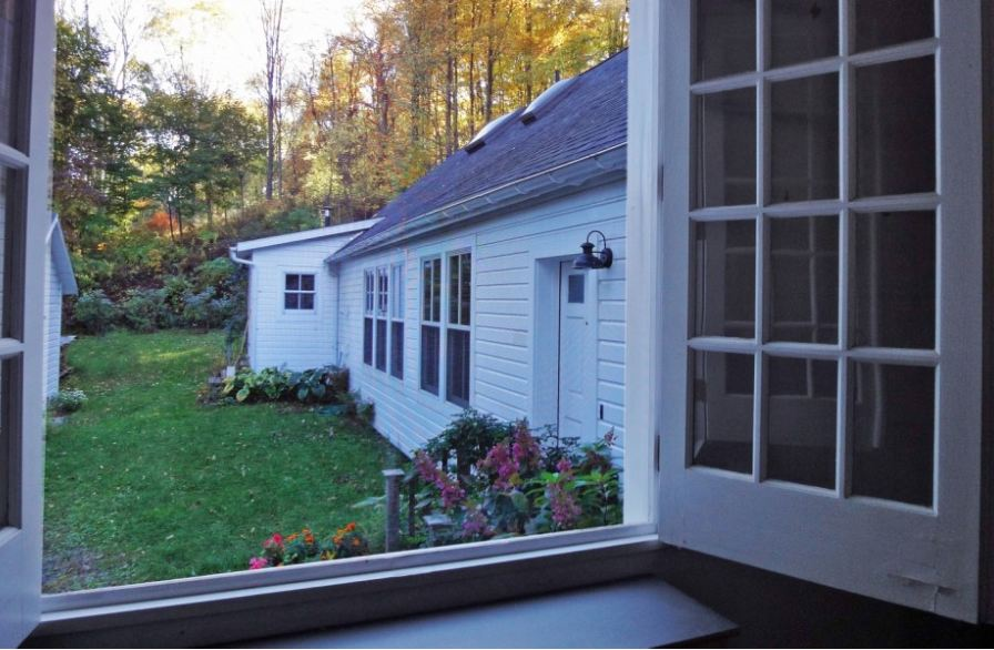 view from open window of side of the house and flower bed