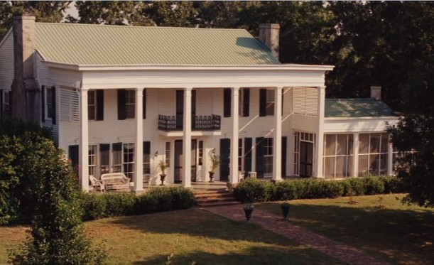 front exterior of white house with pillars and black shutters