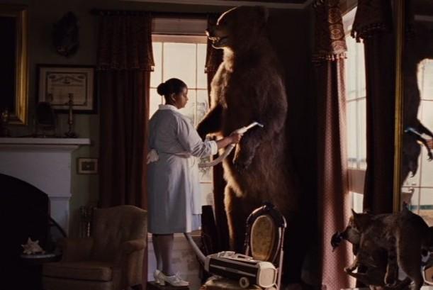 Minnie vacuuming the large stuffed bear in corner of study