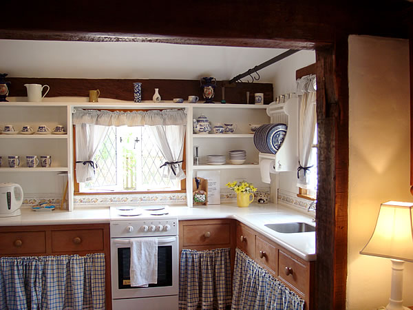 A kitchen with skirted sink and open shelves in cottage