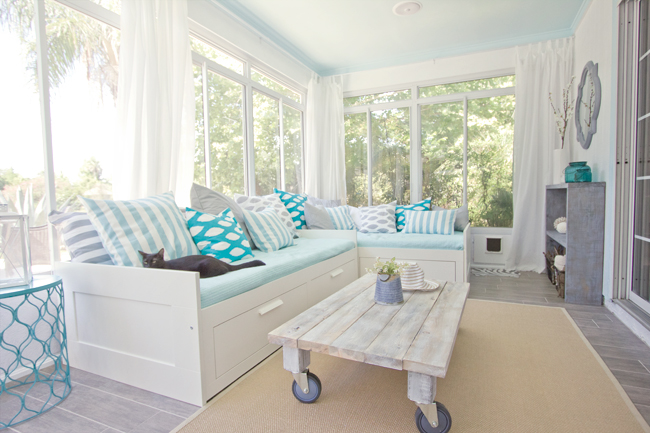 A sunroom with white curtains and sectional sofa