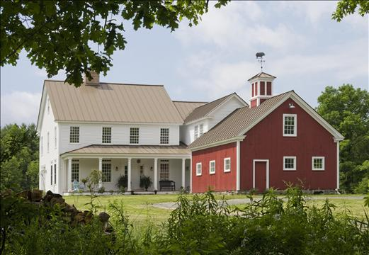 exterior of white house with front porch beside red barn