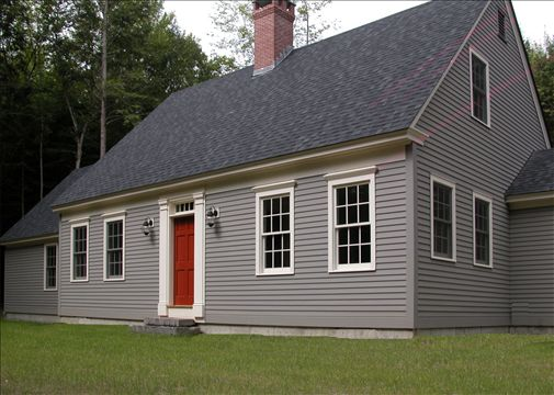 front exterior of cape style home with red door and gray siding