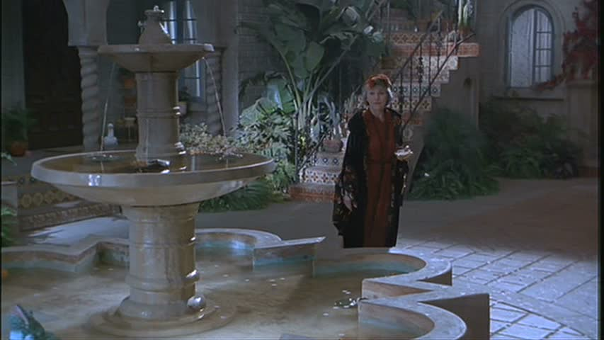 a woman standing beside the fountain at night