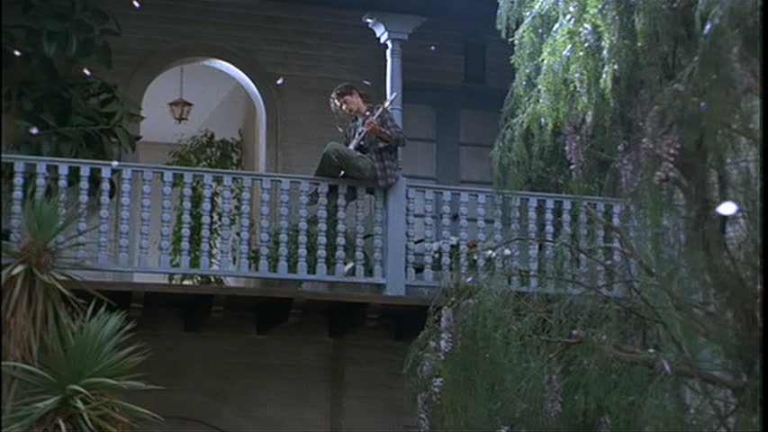 A person sitting on the railing on the upper level above the courtyard