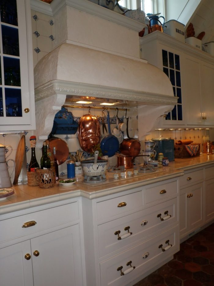 A kitchen with center stove and large vent hood