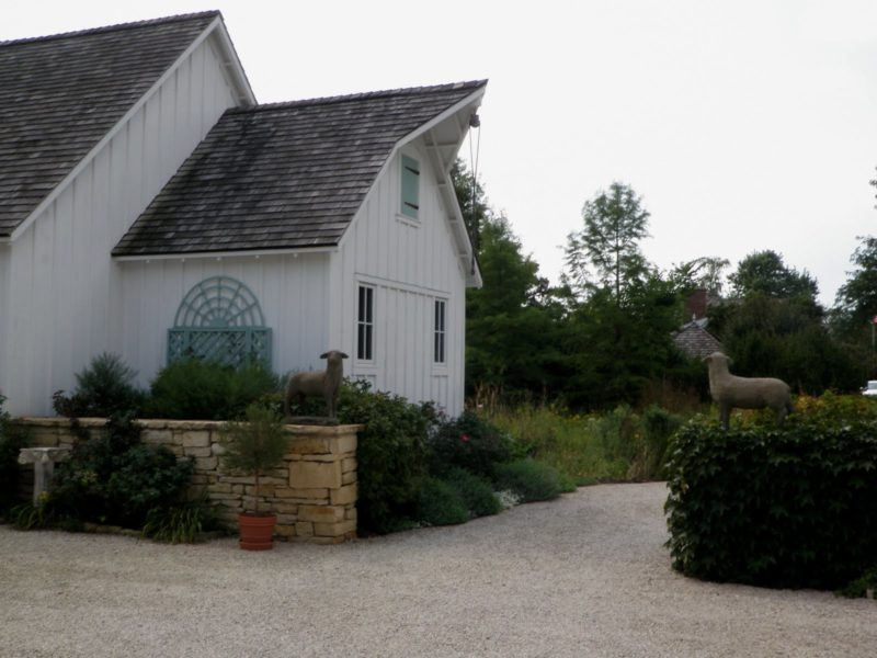 exterior of French Country style farmhouse with stone wall and lamb statue