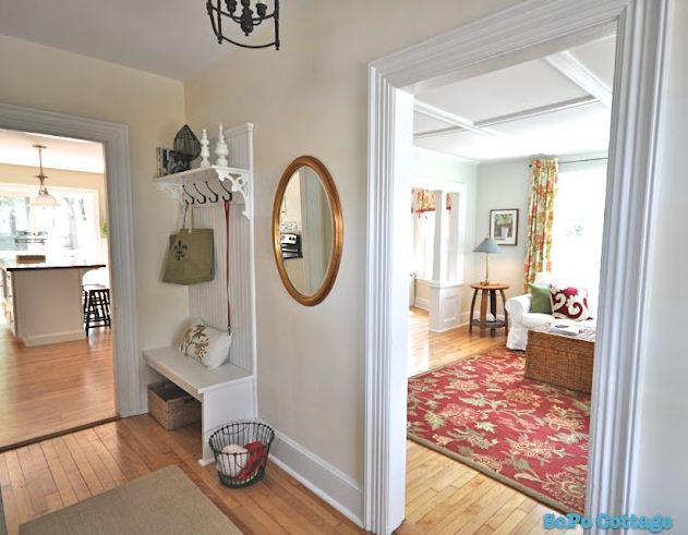 inside entry hall of house with oval mirror and bench