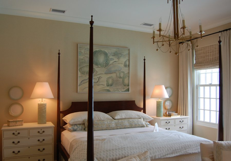 A bedroom with a four poster bed and chandelier