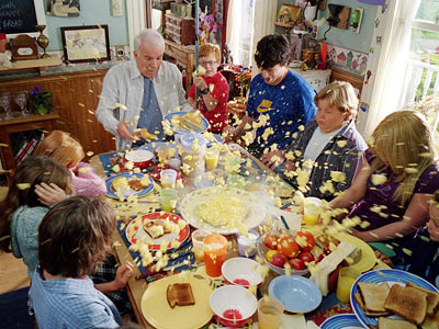 A group of people sitting at a table full of food in Cheaper By the Dozen