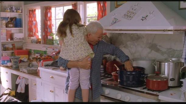Steve Martin standing over stove while holding his character\'s daughter